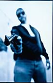 Adult, Adults, Aggressive, Aggressiveness, Aim, Aiming, Arrogance, Arrogant, Blue, Blue tone, Blurred, Close up, Close-up, Closeup, Color, Colour, Contemporary, Crime, Crimes, Criminal, Criminality, Criminals, Danger, Dangerous, Detail, Details, Determin