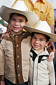 Hispanic boys, brothers, cowboy outfit, hat. Championship Rodeo. Homestead. Florida. USA.