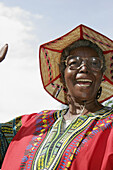 Black senior woman, West African Caribbean outfit, straw hat. 12th Avenue. Miami. Florida. USA.