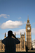 Tourist taking photograph of Big Ben and Houses of Parliament. London. United Kingdom