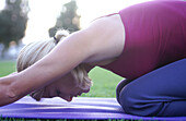 Woman in her mid 20 s doing yoga in the park. Santa Monica. California. USA.