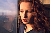 Pensive redhead female stares out window at dusk, New York City, USA