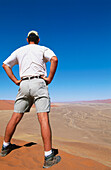 Africa, Arid, Aridity, Back view, Barren, Blue, Blue sky, Color, Colour, Daytime, Desert, Deserts, Dry, Dune, Dunes, Exterior, Full-body, Full-length, Human, Male, Man, Men, Men only, Namibia, Nature, One, One person, Outdoor, Outdoors, Outside, People,