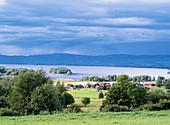 Houses and thunder clouds over lake called Orsa. Naset, Dalarna, Sweden