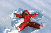 Overhead view of Little Girl Making Snow Angel In Snow