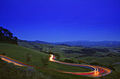 Automobile Light Trails at Dusk on winding mountain road, Volterra,Tuscany, Italy