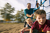 Father and children playing on merry go round at playground