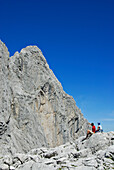 Two hikers resting at Ellmauer Tor with view to Fleischbank, Wilder Kaiser Kaiser mountain range, Tyrol, Austria