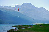 Kite surfer, pedestrians and cyclists at lake Silvaplaner, Upper Engadin, Grisons, Switzerland