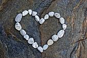 Heart formed with white pebbles on dark rock slab, valley of Verzasca, Verzasca, Ticino, Switzerland