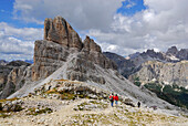 Two hikers in front of Averau, Alta Via delle Dolomiti number one, Dolomites, Cortina, Venezia, Italy