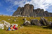 Two hikers resting beneath south wall of Monte Formin, Alta Via delle Dolomiti No. 1, Dolomites, Cortina, Venezia, Italy
