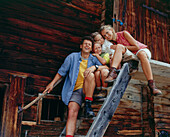 Family sitting on a staircase infront of an alp lodge, Eng, Kleiner Ahornboden, Tyrol, Austria
