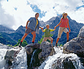 Family crossing a river, Eng, Kleiner Ahornboden, Tyrol, Austria