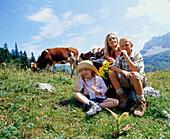 Mother and children sitting on mountain pasture, Eng, Kleiner Ahornboden, Tyrol, Austria