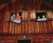 Family looking out of window of an alp lodge, Eng, Kleiner Ahornboden, Tyrol, Austria