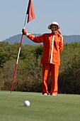 Woman, female caddy holding the flag, Kirimaya Golf Course, Khao Yai National Park, Thailand