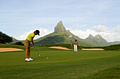 Woman playing golf on a golf course, Tamarin Golf Course, Mauritius, no MR