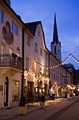 Christmassy decorated and illuminated Ludwigstrasse in the eveining, church Maria Himmelfahrt in background, Partenkirchen, Garmisch-Partenkirchen, Upper Bavaria, Germany