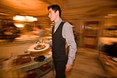 Waiter serving a meal in the restaurant of Hotel Zugspitze, Garmisch-Partenkirchen, Upper Bavaria, Germany