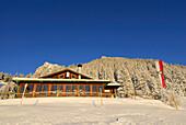 Hut Vorderkaiserfeldenhuette in winter with Tyrolean flag, Zahmer Kaiser, Kaiser range, Kufstein, Tyrol, Austria