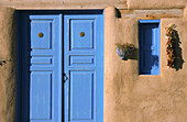 Adobe house with blue door and window. Rancho de Taos. New Mexico. USA