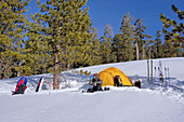 Skier drinking from a bottle in front of a yellow dome tent in a backcountry ski camp, Yosemite National Park, California