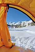 Blue sky over Sierra peaks through the door of a yellow dome tent, Little Lakes Valley, Inyo National Forest, Sierra Nevada Mountains, California