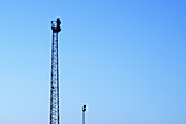 Blue, Blue sky, Color, Colour, Concept, Concepts, Daytime, Engineering, Exterior, Height, Horizontal, Industrial, Industry, Outdoor, Outdoors, Outside, Pair, Platform, Platforms, Silhouette, Silhouettes, Skies, Sky, Surveillance, Tall, Tower, Towers, Two