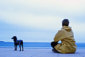 Adult, Adults, Alone, Animal, Animals, Baby boomer, Baby boomers, Back view, Blue, Calm, Calmness, Color, Colour, Companion, Companions, Contemporary, Daytime, Dog, Dogs, Exterior, Female, Full-body, Full-length, Future, Ground, Grounds, Horizon, Horizon