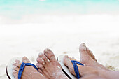 Adult, Adults, Beach, Beaches, Body, Body part, Body parts, Close up, Close-up, Closeup, Color, Colour, Contemporary, Couple, Couples, Daytime, Exterior, Feet, Female, Flip flop, Flip flops, Flip-flop, Flip-flops, Foot, Holiday, Holidays, Human, Leisure,