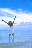 Adult, Adults, Alone, Arms raised, Back view, Beach, Beaches, Blue, Calm, Calmness, Chill out, Chilling out, Cloud, Clouds, Coast, Coastal, Color, Colour, Contemporary, Daytime, Exterior, Female, Full-body, Full-length, Gesture, Gestures, Gesturing, Happ