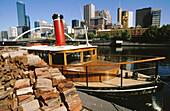 Tourist steamer on Yarra River with CBD at the background. Melbourne. Victoria, Australia