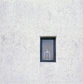 Oil lamp in small window. Sweden.