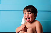 Anticipation, Boy, Boys, Carefree, Caucasian, Caucasians, Child, Childhood, Children, Children only, Color, Colour, Contemporary, Dark-haired, Delicious, Eat, Eating, Facial expression, Facial expressions, Facing camera, Food, Grin, Grinning, Happiness,