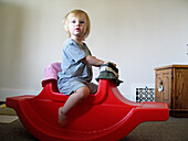 18 month old toddler playing on red rocking horse in her home