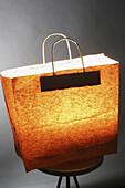 Bag, Bags, Close up, Close-up, Closeup, Color, Colour, Commerce, Concept, Concepts, Idea, Ideas, Indoor, Indoors, Interior, Light, Paper bag, Shopping, Still life, Stool, Stools, Trade, J11-488649, agefotostock