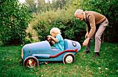 5-10 Jahre, 60-70 Jahre, 65-70 Jahre, 70-80 Jahre, Alte Leute, Altmodisch, Außen, Auto, Autos, Enkel, Enkelkinder, Erholen, Erholung, Erwachsene, Erwachsener, Familie, Familien, Farbe, Freizeit, Ganzkörper, Ganzkörperaufnahme, Garten, Gärten, Großvater,