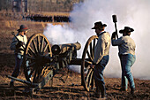 Confederate artillery battery fires during a reenactment of the Battle of Stones River, near Stones River National Battlefield. Murfreesboro. Tennessee. USA