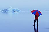 Allein, Alleine, Außen, Bewegung, Blau, Eine Person, Eins, Einzeln, einzig, Farbe, Fremd, Ganzkörper, Ganzkörperaufnahme, Gehen, Gehend, Gehende, Horizontal, Kalt, Kälte, Lifestyle, Mensch, Menschen, Regenschirm, Regenschirme, Schirm, Schirme, Seltsam, S