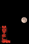 Neon Motel sign with full moon in background