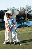 Mature man teaching boy to play golf