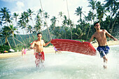 Two young men running into the water with airbed at the beach
