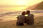 Young couple sitting on sand at the beach kissing at sun set