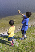 Boys with slingshot by the lake
