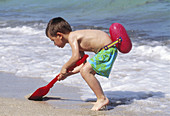 Boy with shovel at the beach
