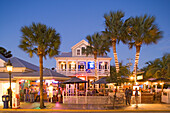 People sitting on the illuminated terrace of a bar in the evening, Duval Street, Key West, Florida Keys, Florida, USA