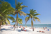 People at a palm beach under blue sky, Smathers Beach, Key West, Florida Keys, Florida, USA