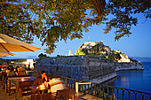 People sitting in the cafe Akteion in the evening, in the background the old citadel, Corfu, Ionian Islands, Greece