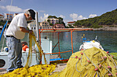 Cephalonia, fisherman cleaning a fishing net at the harbour Assos, Ionian Islands, Greece